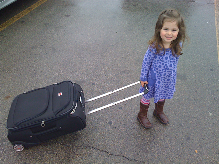 Anneliese rolling a suitcase